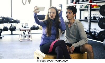 Fit couple in crossfit gym taking selfie with smartphone. -...
