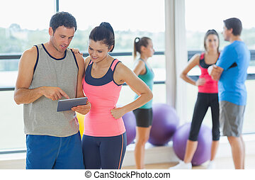 Fit couple looking at digital table with friends chatting in...