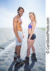 Fit couple rollerblading together on the promenade on a...
