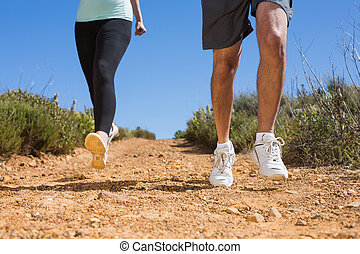 Fit couple running down mountain trail