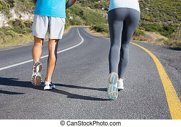 Fit couple running together down a road