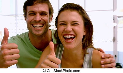 Fit couple showing thumbs up to cam