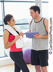 Fit couple with at digital table in exercise room - Fit...