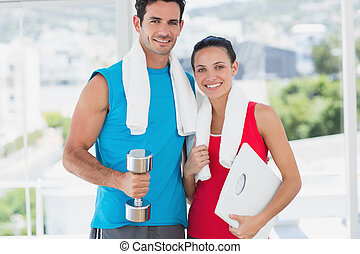 Fit couple with dumbbell and scale in bright exercise room -...