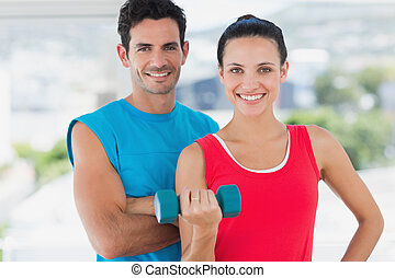 Portrait of a fit young couple standing with dumbbell in a bright exercise room