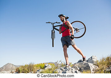 Fit cyclist carrying his bike on rocky terrain on a sunny ...