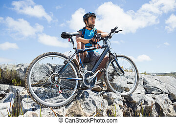 Fit cyclist taking a break on rocky peak