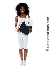 Fit female athlete holding weighing machine