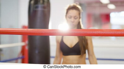 Fit female boxer resting with her arms on the ring ropes
