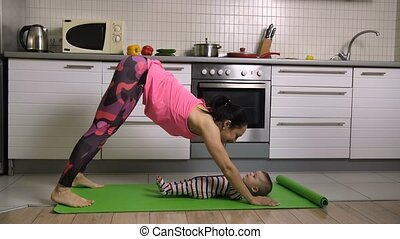 Fit female doing yoga together with baby at home