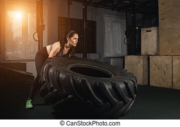 female flipping tire at the gym.