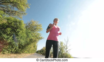 Fit female runner running on countryside road