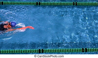 Fit female swimmer doing the back stroke in swimming pool in slow motion