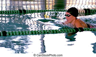 Fit female swimmer doing the butterfly stroke in swimming pool in slow motion