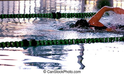 Fit female swimmer doing the front stroke in swimming pool...