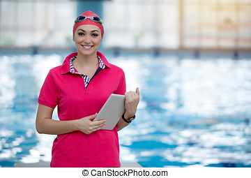 Fit female swimming trainer with tablet at the pool