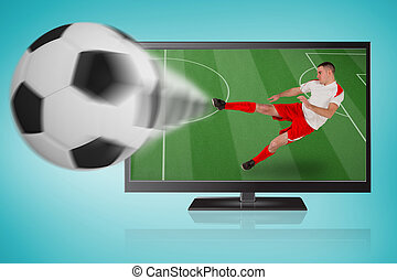 Fit football player playing ball out of tv and kicking against blue vignette