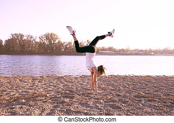 girl exercise by the lake sunny autumn day, full body shot, handstand