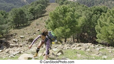 Fit girl climbing hill - Young beautiful female in casual...