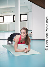Fit girl doing plank exercise in the gym.