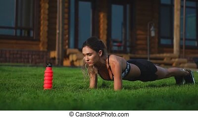 Fit girl doing plank exercise outdoor in the park warm...