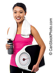 Fitness instructor holding weight scale and sipper bottle