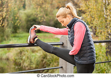 Fit girl is stretching in the park