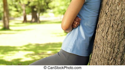 Fit girl leaning against tree in the park on a sunny day