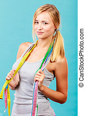 Fit girl with many colorful measure tapes on blue
