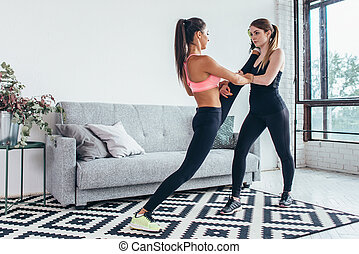 Fit girls preparing legs workout. Leg stretching exercise fitness woman doing warm-up, hamstring muscles stretch standing at home.