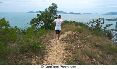 Fit handsome athletic male working out. Man run on mountain with city view