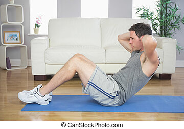 Fit handsome man doing sit ups in bright living room