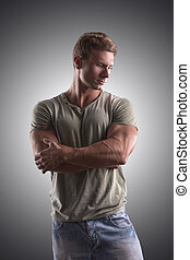 Fit handsome young man standing confident, arms crossed