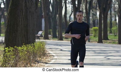 Fit jogger running in park taking a break and setting his fitness tracker smart watch