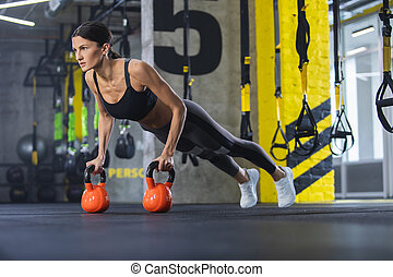 Fit lady is concentrating on work out with outfit