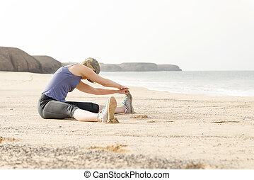 Fit Lady Sitting on a Beach Doing Leg Stretches