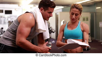 Fit man and trainer talking
