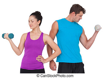 Fit man and woman lifting dumbbells on white background