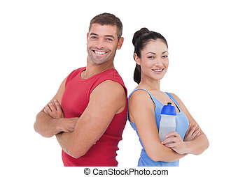Fit man and woman smiling at camera together