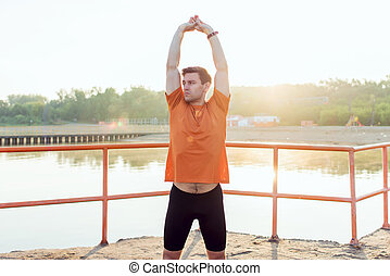 Fit man athlete doing arm stretches warming up before jogging.