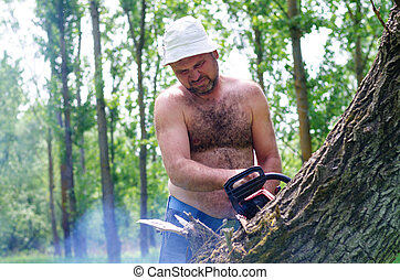 Fit man carrying a chainsaw in woodland