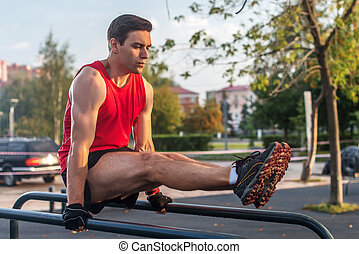 Fit man doing abdominal exercise on parallel bars in summer park.