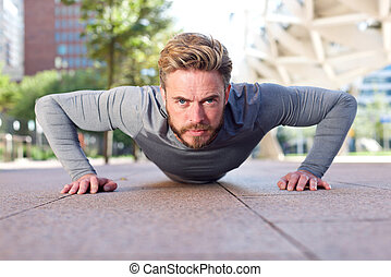 Fit man doing push ups outdoors
