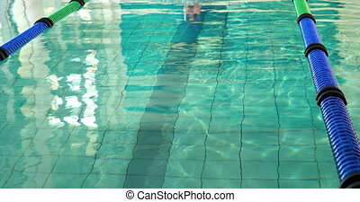 Fit man doing the breast stroke and smiling at camera in...