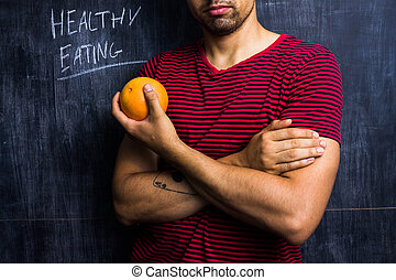 Fit man holding a grapefruit in front of blackboard