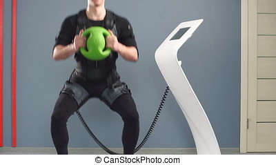Fit Man in electric muscular suit to stimulate with training...