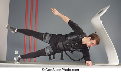 Fit Man in Electrical Muscular Stimulation Suits Doing Side...