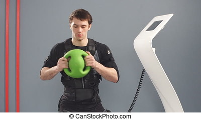 Fit Man in EMS suit training with medecine bal, - Fit Man in...