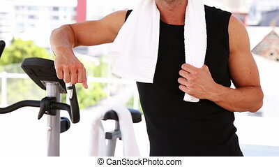 Fit man leaning on exercise bike - Fit man leaning on...