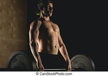 Fit man lifting barbells looking focused, working out in a gym